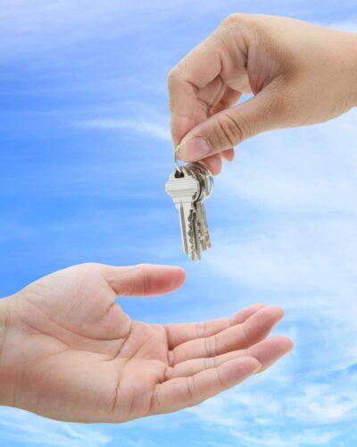 9427249 - man handing over the set of keys house against blue sky